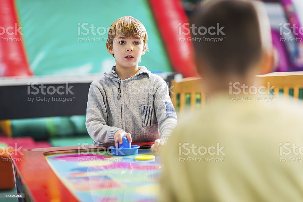 Boys playing air hockey. stock photo