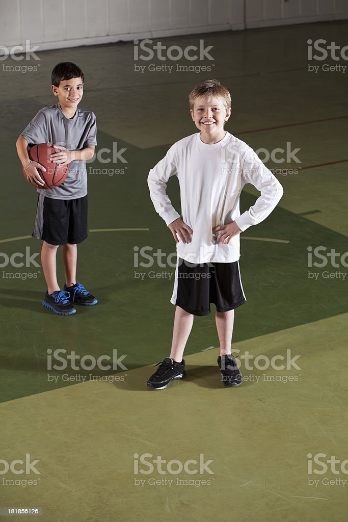 Boys playing basketball in gym stock photo