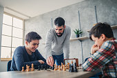 Two boys playing chess while father/teacher watching them