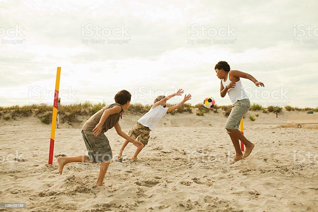 Boys playing football on beach royalty-free stock photo