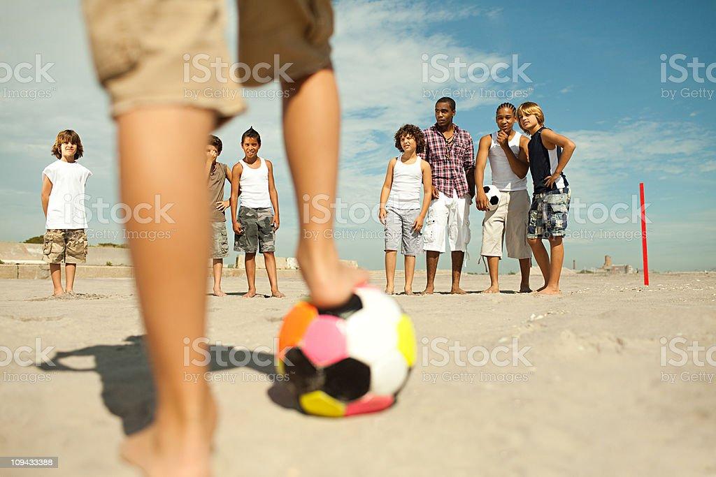 Boys playing football on beach stock photo