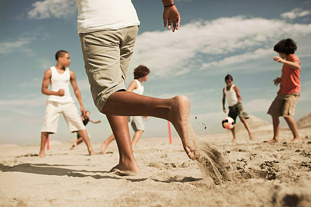 jungs spielen fußball am strand - kinderfüße stock-fotos und bilder
