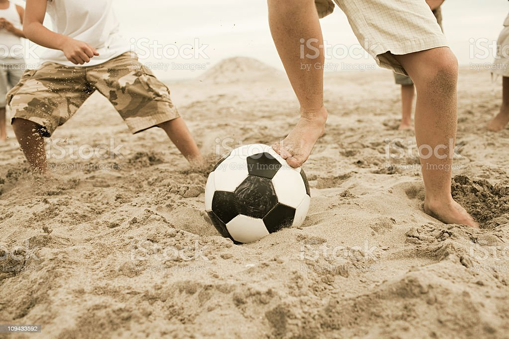 Boys playing football on beach stock photo