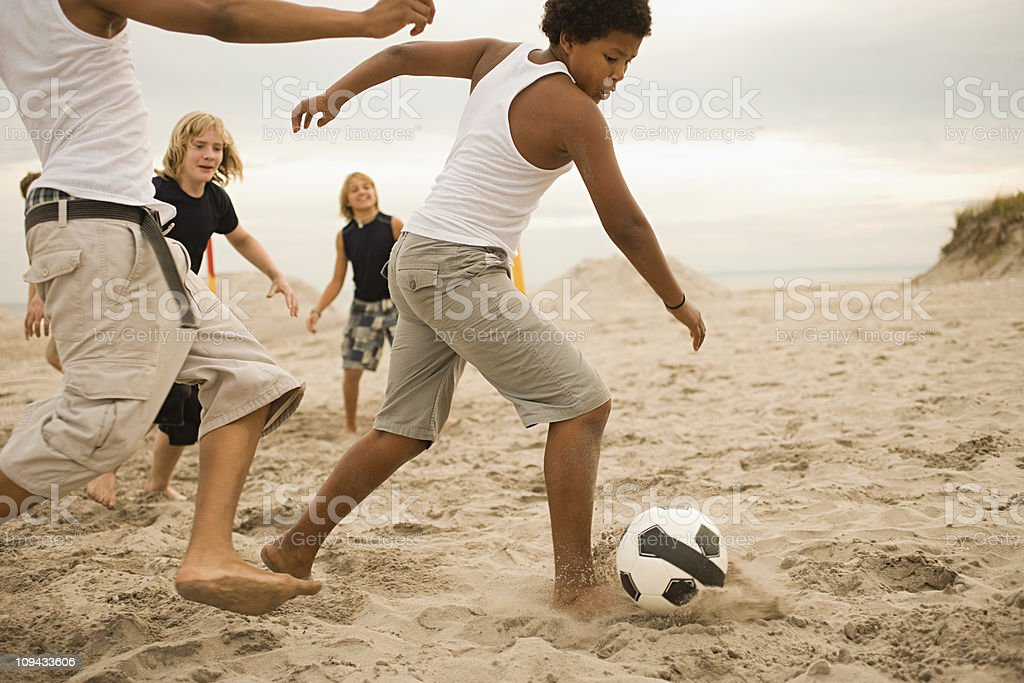 Boys playing football on beach royalty-free stock photo
