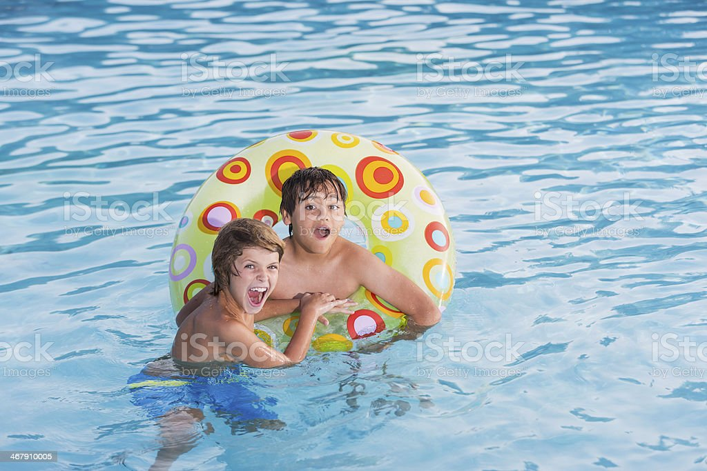 Boys playing in swimming pool. stock photo