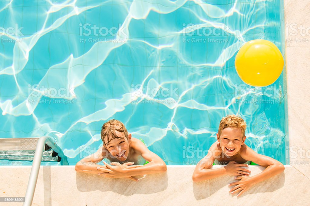 Boys playing in swimming pool stock photo
