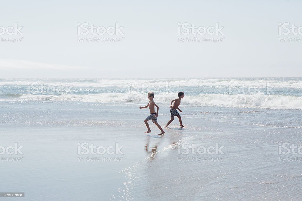 Boys playing on a beach together stock photo