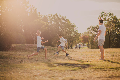 Two young boys and their older brother playing soccer in the park.