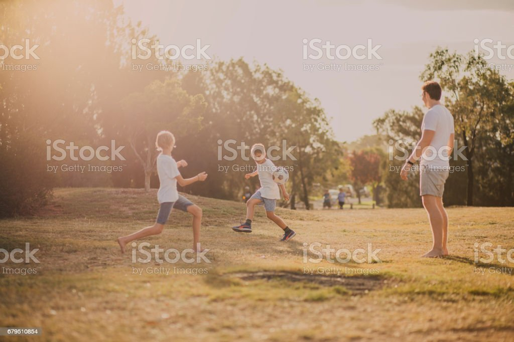 Boys Playing Soccer in the Park stock photo