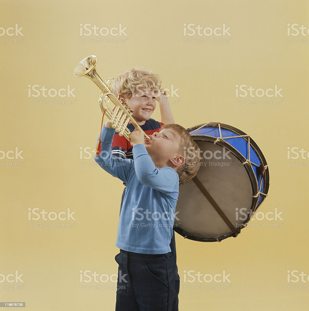 Boys playing trumpet and drum, smiling stock photo
