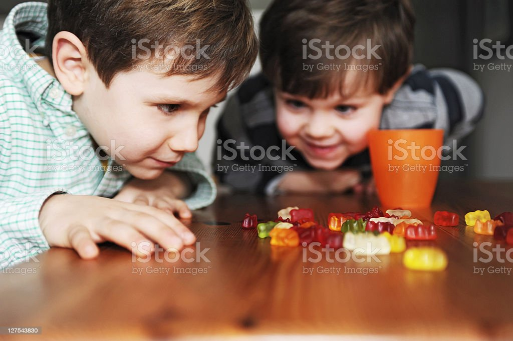 Boys playing with candy at table stock photo