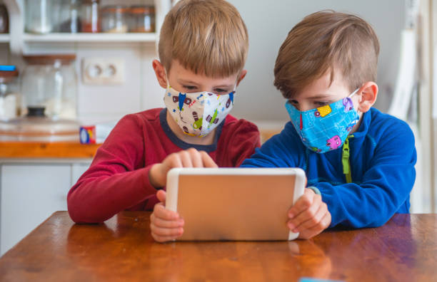 Boys Playing With Digital Tablet And Wearing Protective Face Mask Boys Playing With Digital Tablet And Wearing Protective Face Mask pollution mask stock pictures, royalty-free photos & images