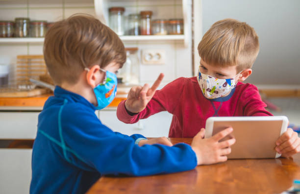 Boys Playing With Digital Tablet At Home, Wearing Protective Masks stock photo
