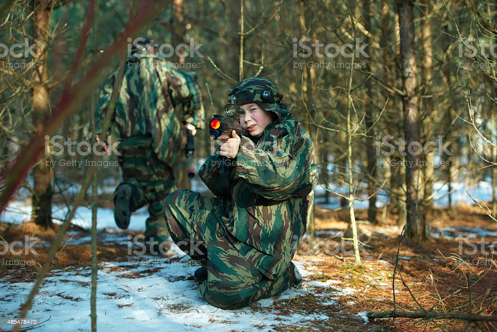 boys playing with gun during laser tag stock photo