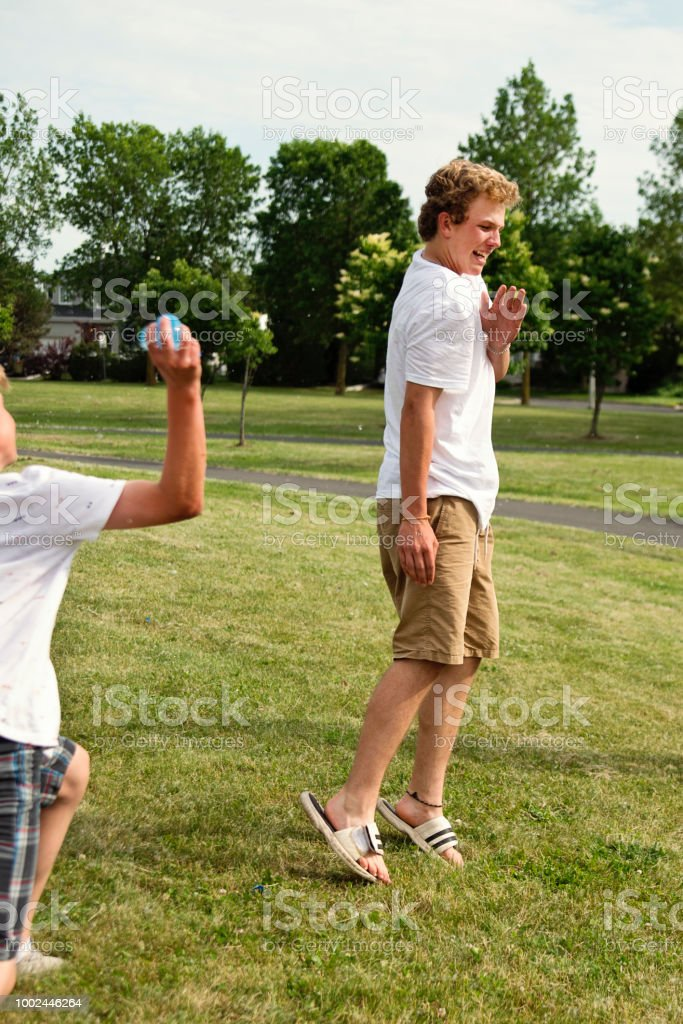Boys playing with water filled ballons in suburb park. stock photo
