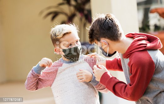 Two boys putting on protective face masks as they leave home. They are going out during the covid-19 pandemic when face masks and social distancing are encouraged to prevent spread of the coronavirus. The brothers are mixed race Caucasian and Hispanic, 8 and 11 years old. The older boy is making sure his younger brother's mask is put on properly.