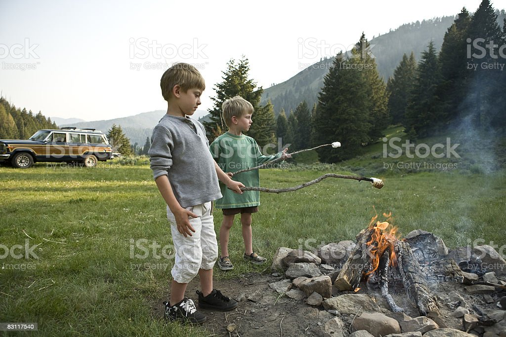Boys roasting marsh mellows by camp fire. photo libre de droits