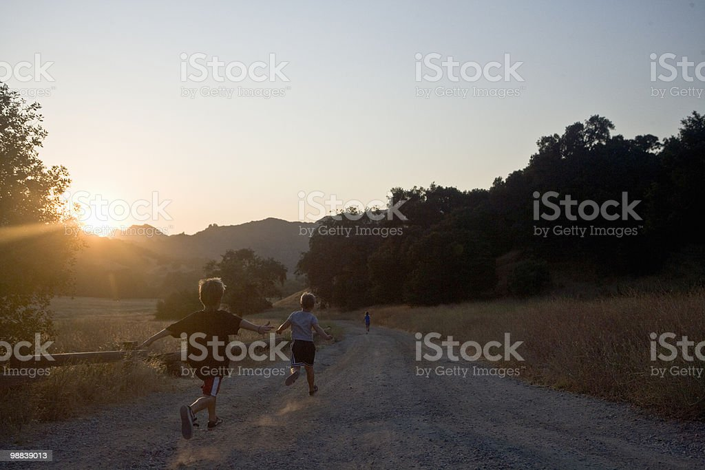 Boys running down gravel road royalty-free stock photo