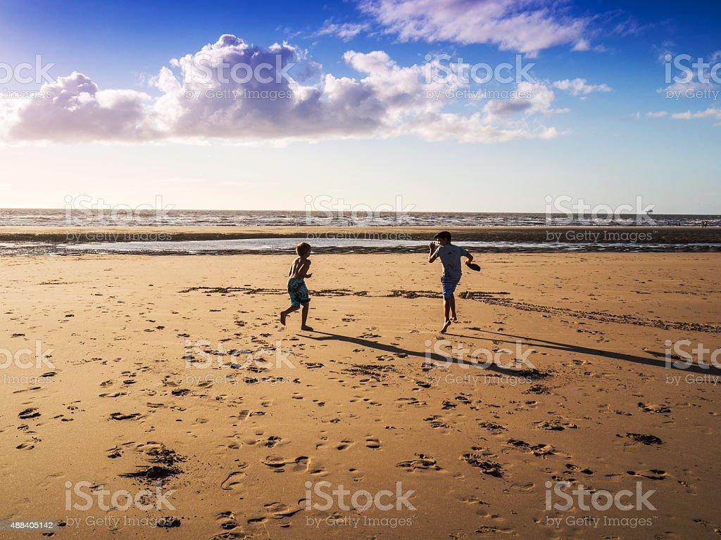 Boys running on the beach in Merseyside, United Kingdom stock photo