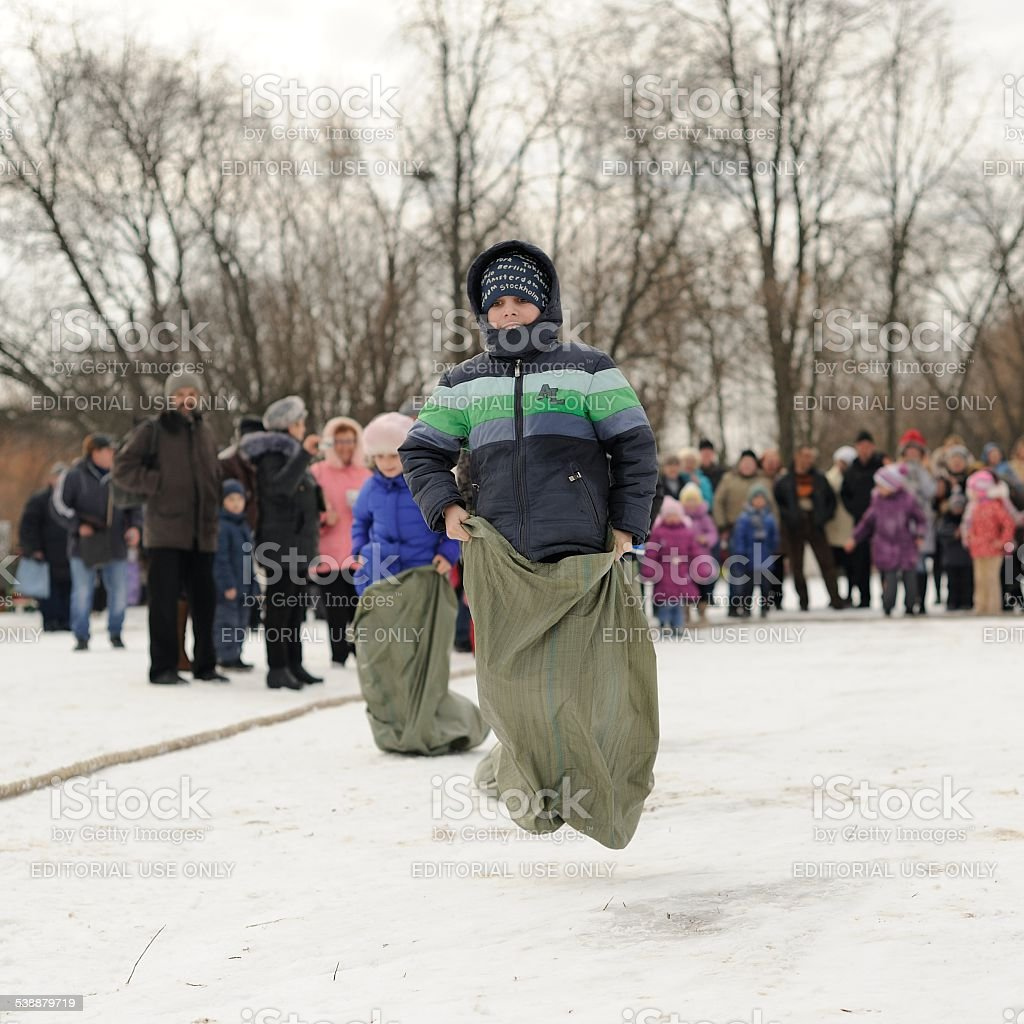 Boys sack-racing during winter Maslenitsa carnival in Russia stock photo