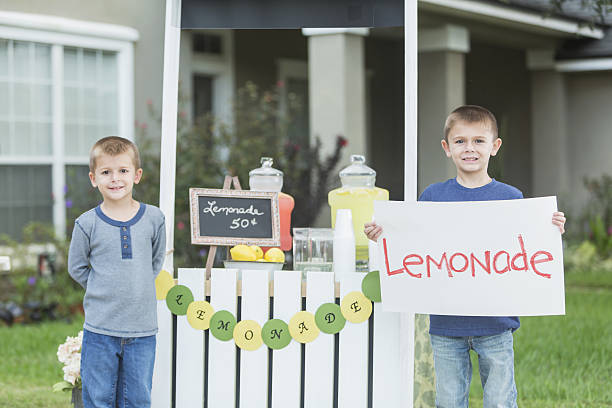 Boys selling lemonade in front yard Two boys with a lemonade stand in their front yard. The older brother is holding a handmade sign. lemonade stand stock pictures, royalty-free photos & images