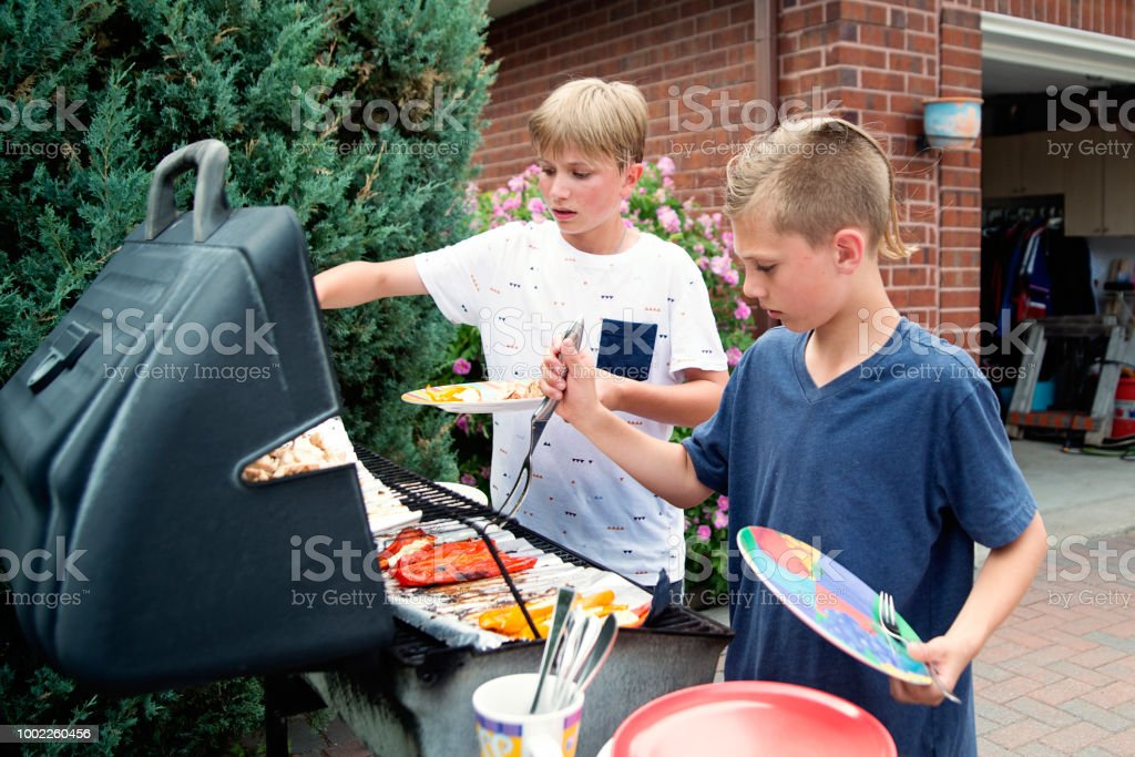 Boys serving themselves on family barbecue. stock photo