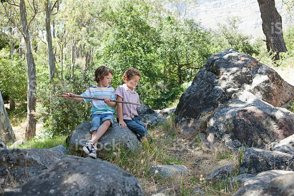 Boys sitting on rocks with stick foto de stock royalty-free