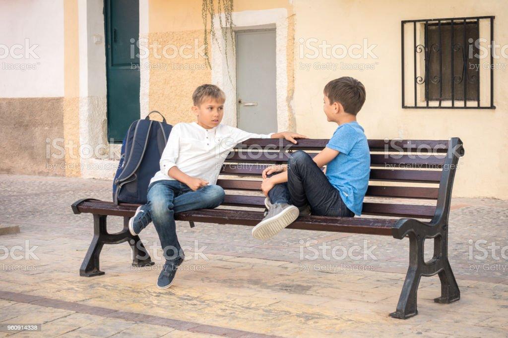 Jungs auf der Bank im Freien sitzen und reden - Lizenzfrei Beige Stock-Foto