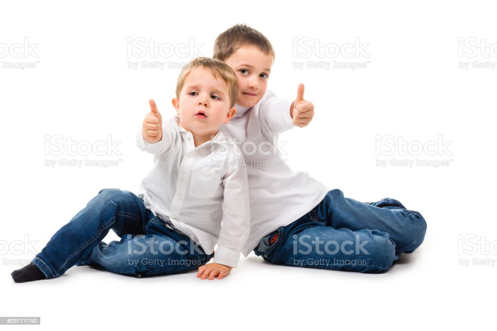 2 boys sitting thumbs up stock photo