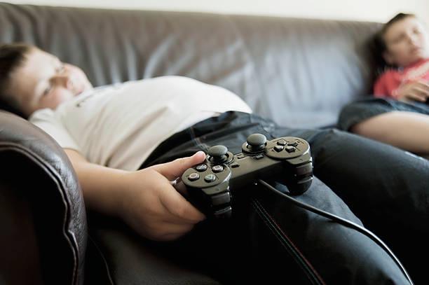 Meninos dormindo no sofá enquanto segura Consoles de jogos - foto de acervo