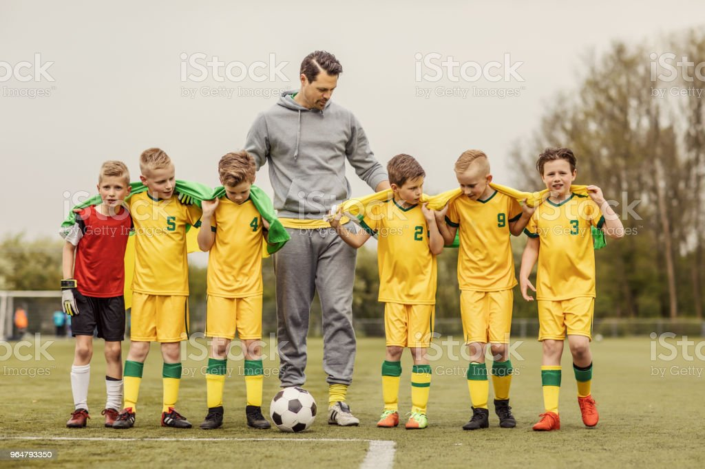 A boys soccer team celebrating a victory with their male coach posing for a group photo royalty-free stock photo