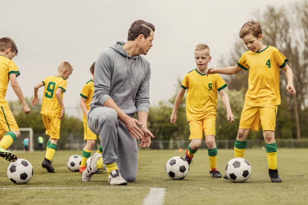 A boys soccer team during an intense football training session with a handsome male coach stock photo
