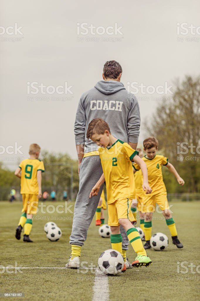 A boys soccer team during an intense football training session with a handsome male coach royalty-free stock photo