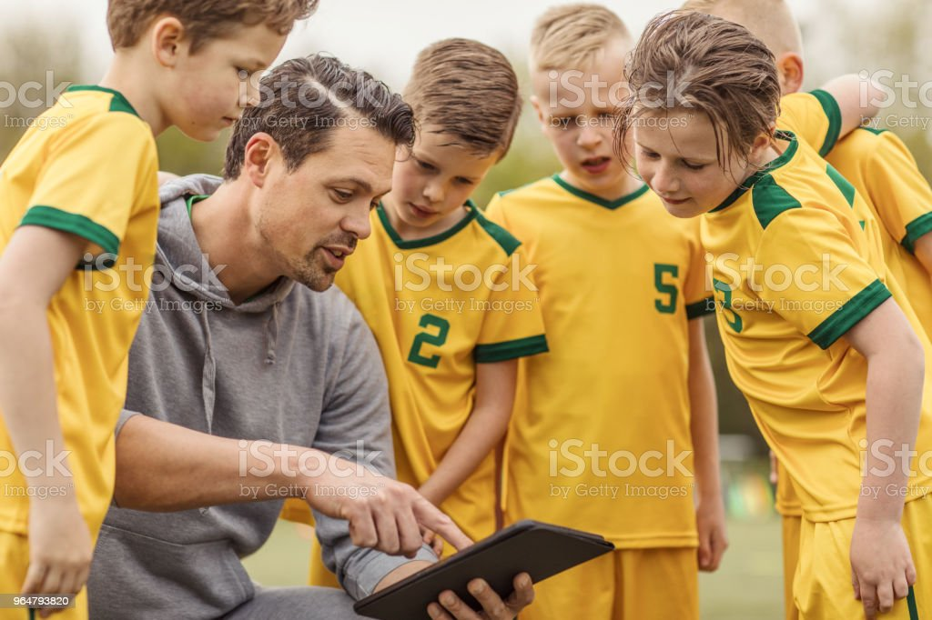 A boys soccer team looking at tactics on a tablet with their male coach during a match royalty-free stock photo