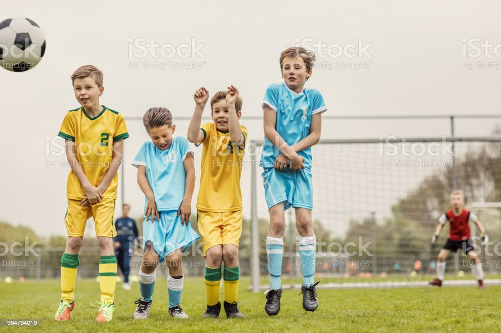 A Boys soccer team making a wall for a free kick during a football match royalty-free stock photo