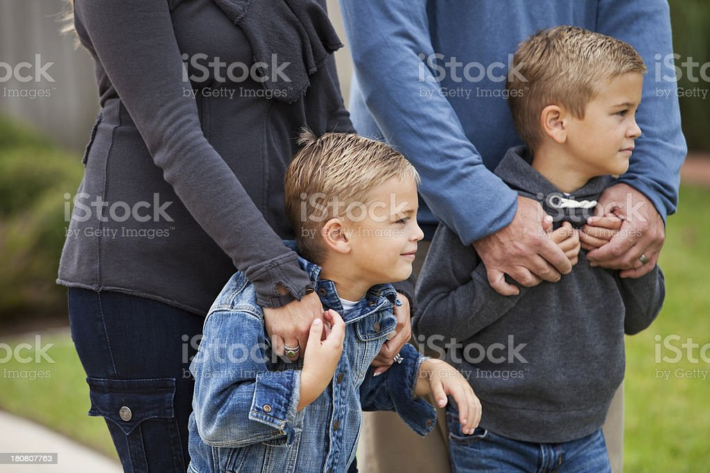 Boys standing with parents outdoors stock photo