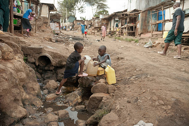 Boys take water on a street of Kibera, Nairobi, Kenya. stock photo