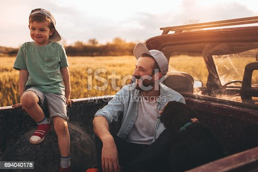 Photo of young father bonding with his boy during the ride in a family pick-up truck, outdoors in the nature. They are in a company of a family dog.