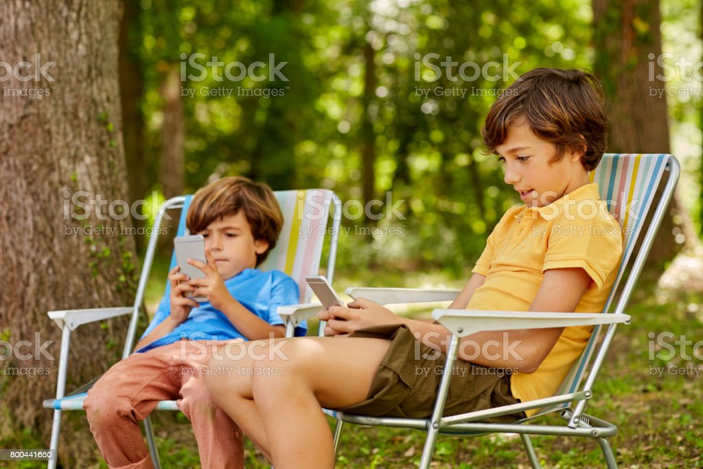 Boys using phones while sitting on deck chairs stock photo