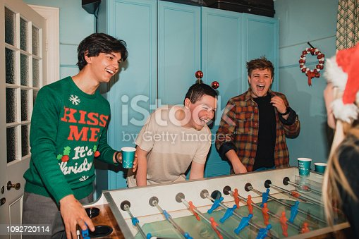 Three young men are playing a game of foosball at a Christmas house party against their girlfriends.
