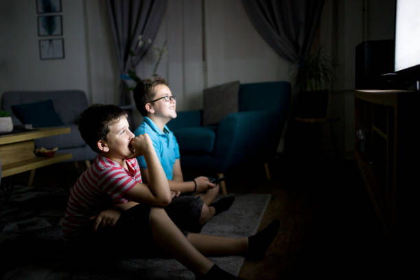 Boys watching a movie at home at night stock photo