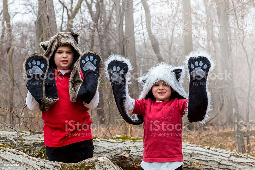 Boys wearing animals hats raise their arms showing paws up stock photo