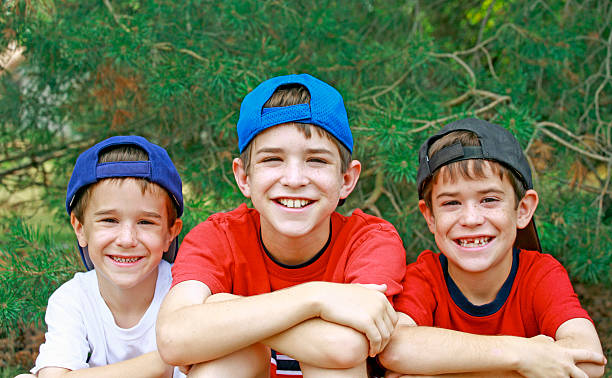 Boys Wearing Baseball Hats Three Boys Wearing Baseball Hats Backwards bending over backwards stock pictures, royalty-free photos & images