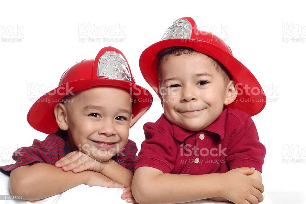 Boys wearing fireman hats 4 and 5 years old stock photo
