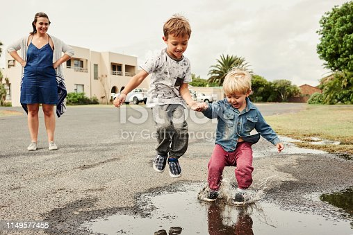 Shot of two adorable little boys playing on the street with their mother watching in the background