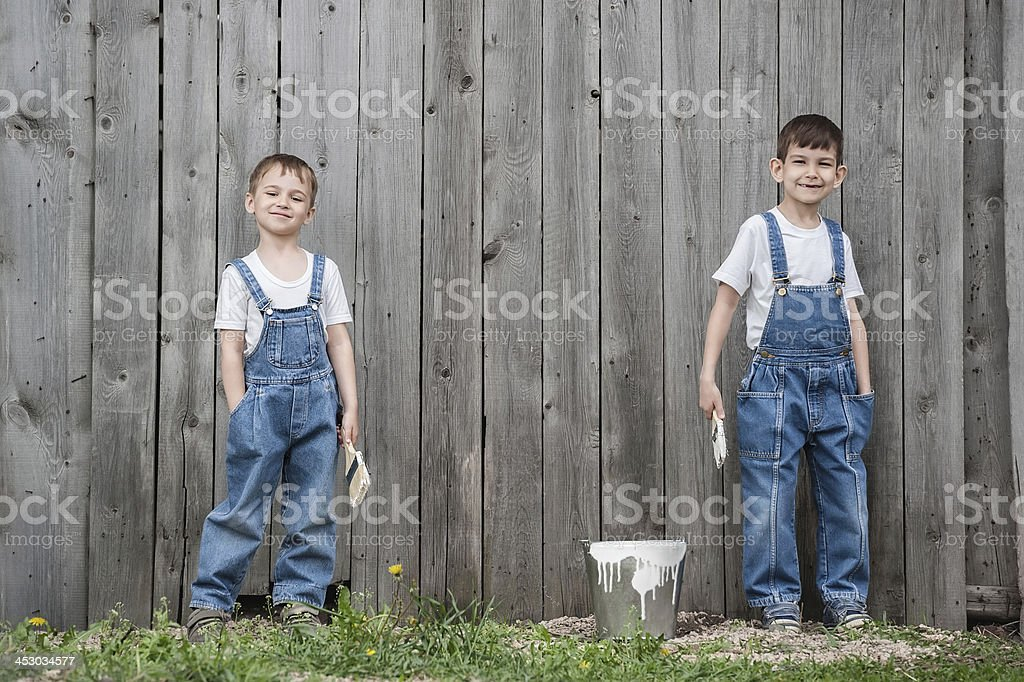 Boys with brushes and paint at an old wall stock photo