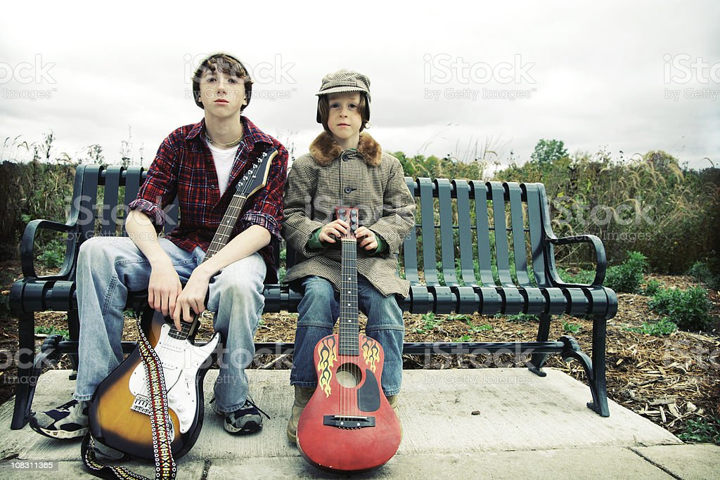 Boys with Guitars Sitting on Bench stock photo