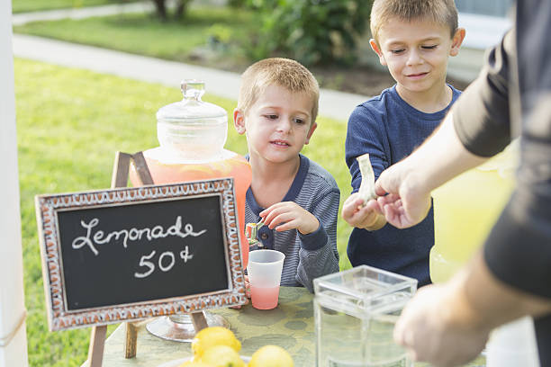 Boys with lemonade stand, taking payment from man Two boys selling lemonade in their front yard. They are serving pink lemonade to a customer, cropped so only his arms are visible, he is handing cash to the older brother. lemonade stand stock pictures, royalty-free photos & images