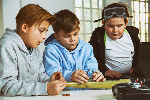 Boys at tech workshop taking things apart and studying how they work. Making eemote controled model airplane.