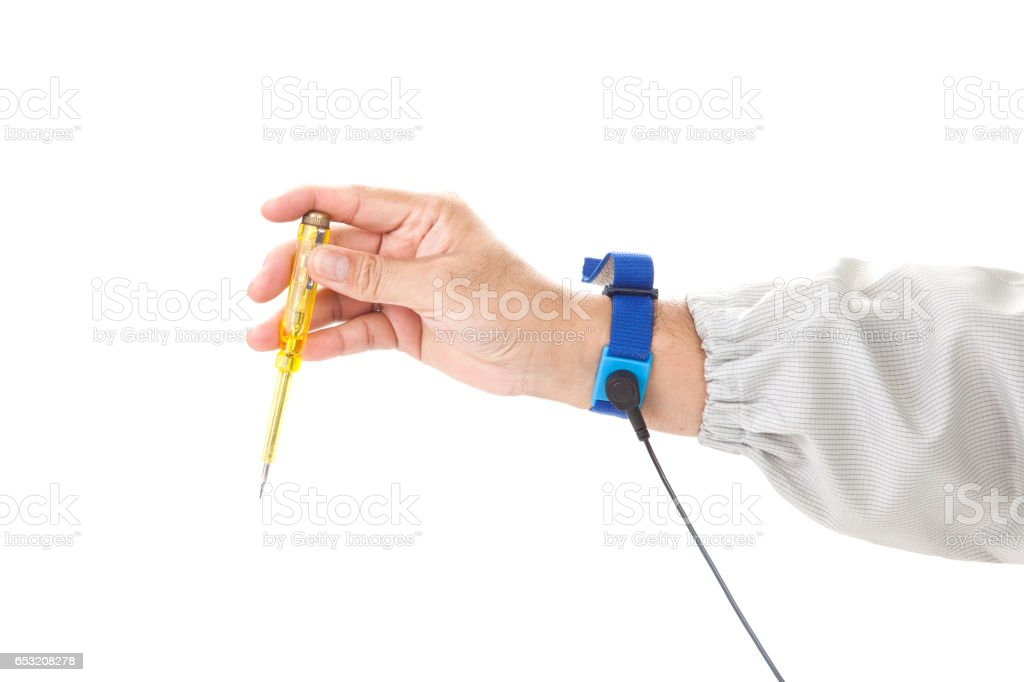 Bracelet on the hand of a man wearing ESD cloth holding a screwdriver, static resistance (ESD) bracelet or ground equipment, anti-static, used to safely ground is working. electronic devices stock photo